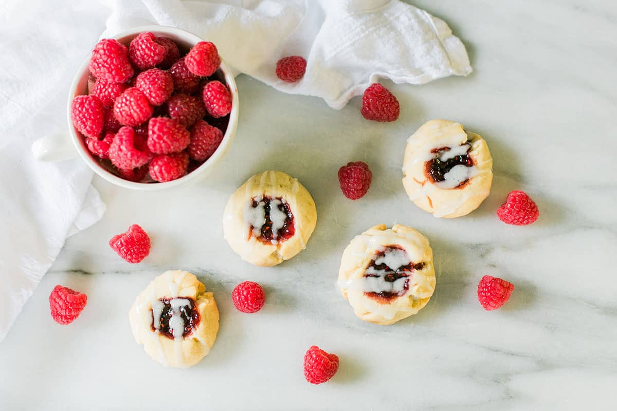 Raspberry Shortbread Tea Cookies: a classic English tea party cookie filled with raspberry preserves. Bright, colorful, and oh so sweet!