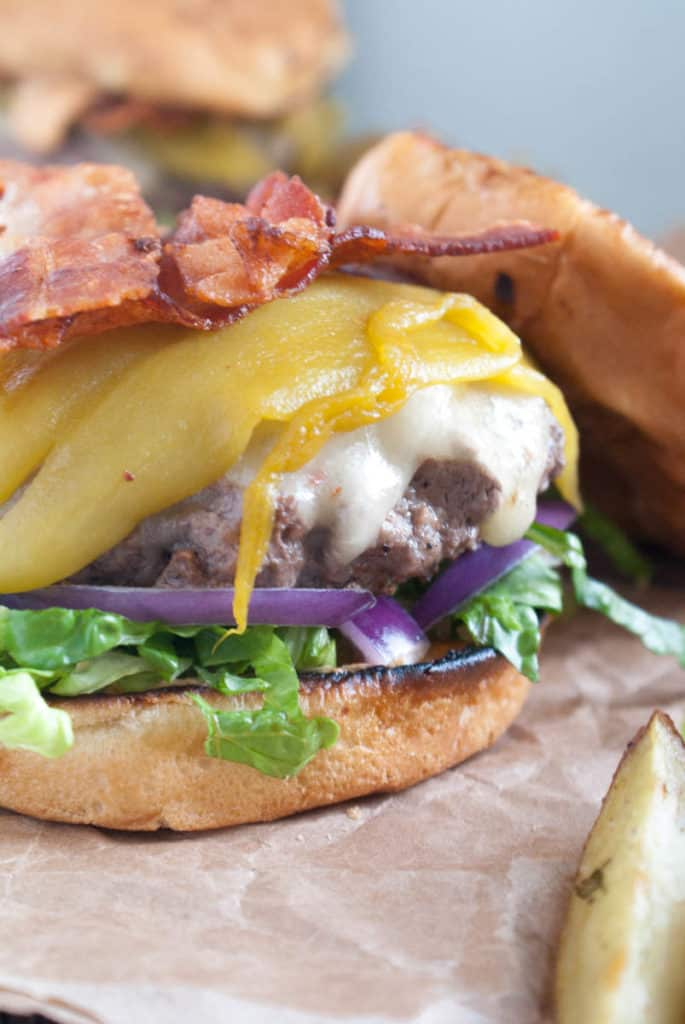 Ortega Burgers: the most flavorful Ortega Burger recipe out there! Toasted Onion buns, 1/2 lb peppercorn crusted beef patties, lettuce, onion, bacon, Ortega chiles, and topped with chipotle aioli.