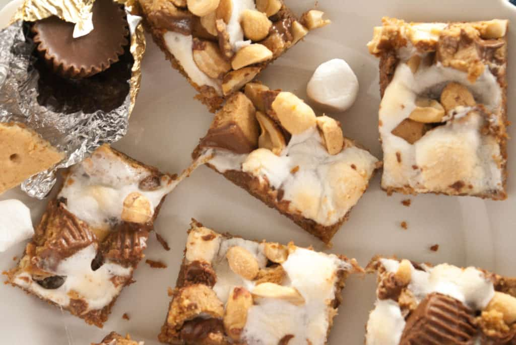 Reese's S'mores Cookie Bars! With a graham cracker cookie base, this treat is loaded with gooey marshmallows, melty Reese's peanut butter cups, salty peanuts and a drizzle of chocolate sweetened condensed milk.