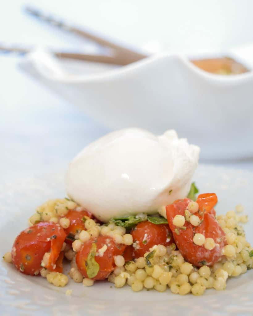 Pesto Pearl Couscous with burrata and tomatoes. This dish is great for potlucks because it can be made ahead of time, doesn't need to be heated up and is so yummy! Full recipe is at femalefoodie.com!