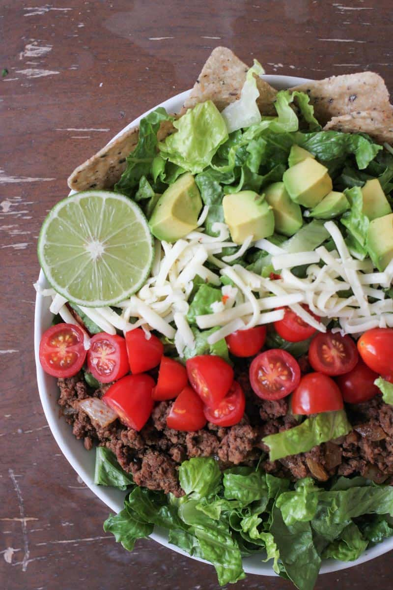 This Easy Taco Salad with homemade buttermilk cilantro dressing is my favorite go-to quick dinner! It is loaded with vegetables, cheese, ground beef, and takes less than 10 minutes to make! Full post at femalefoodie.com.