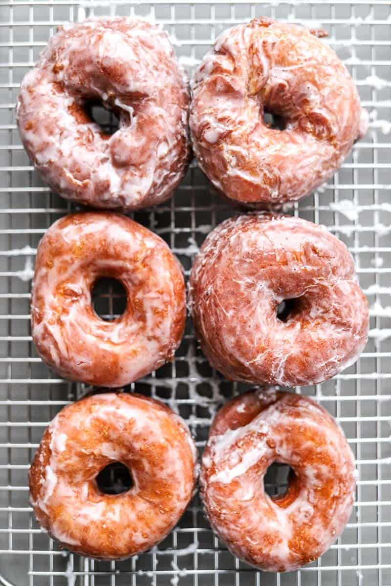 six glazed donuts on cooling rack