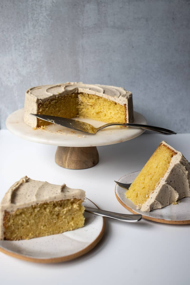 two slices of olive oil cake with remainder of whole cake on stand